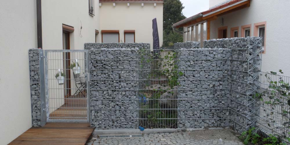 Eingangsbereich zu einem privaten Garten mit Steinmauern. Private Referenzen.