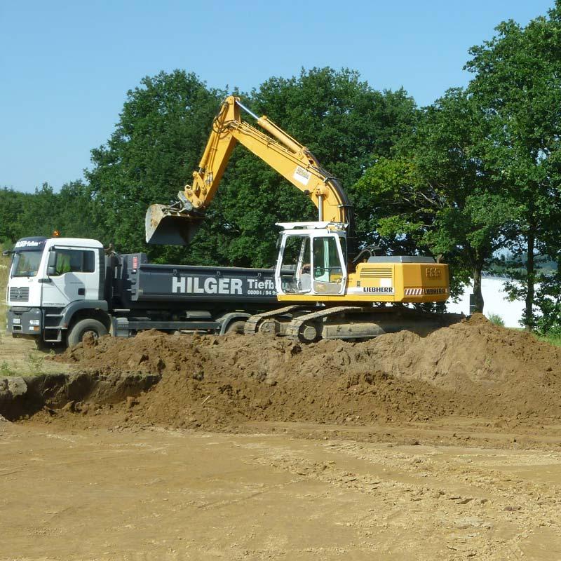 Erdreich wird auf einen LKW der Hilger Tiefbau GmbH verladen.