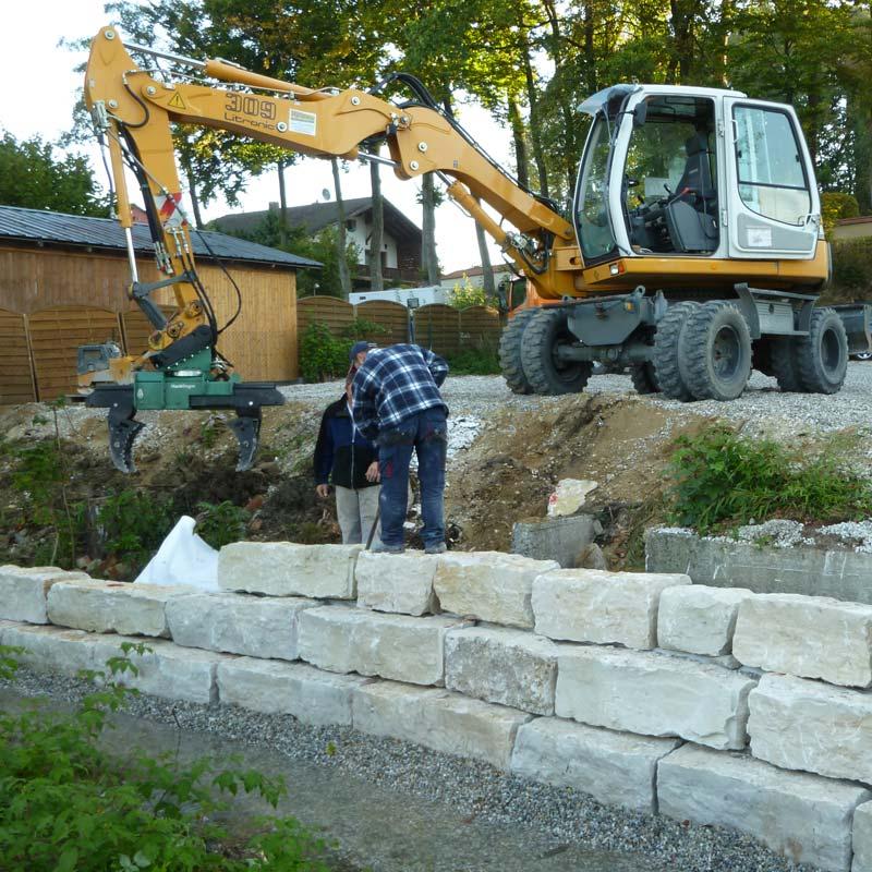 Mauersteine im Garten werden gesetzt.