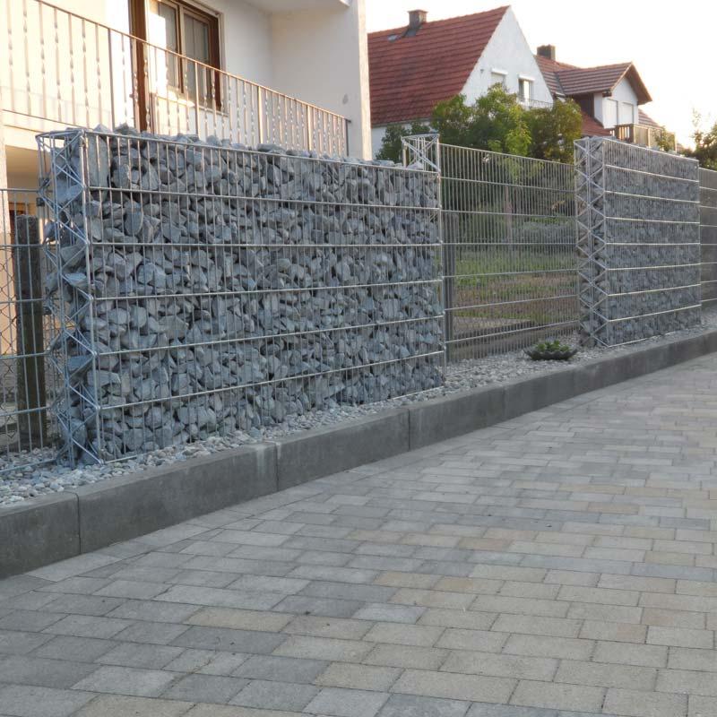 Zaun mit Steinschüttung in einer Einfahrt.